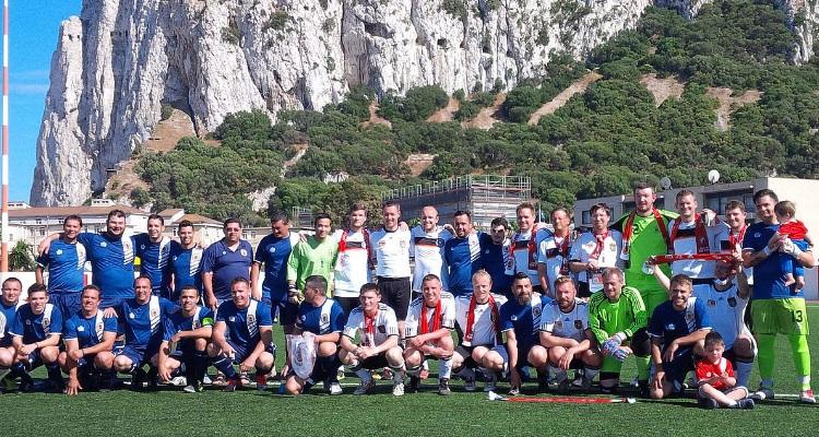 Sportmarketing-Agentur W-com organisiert in Gibraltar ein Fan-Match. Mannschaftsfoto mit beiden Teams vor einer traumhaften Kulisse mit dem Affenfelsen.