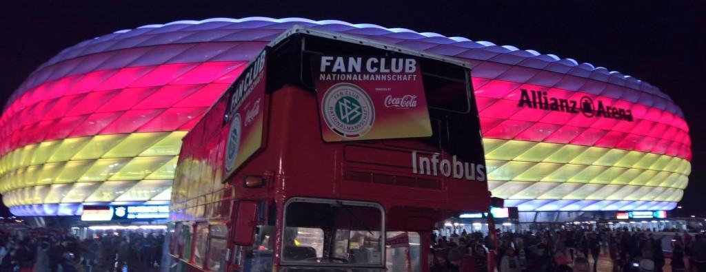 Der Fan Club-Bus vor der Allianz Arena, die in München in schwarz rot gold erscheint.